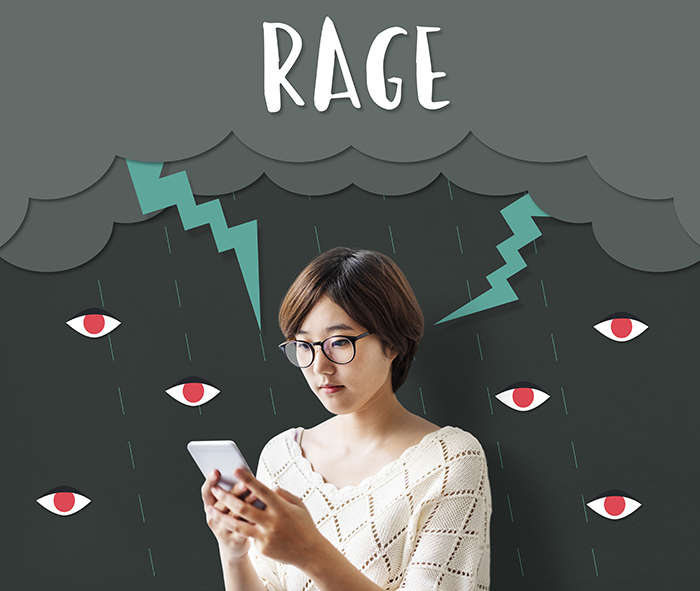 girl on phone under banner of rage