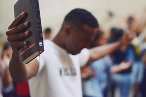 youth holding out Bible